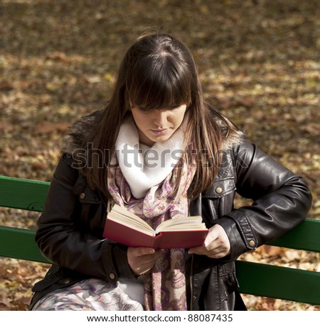 Beautiful woman sitting on a park bench and reading a book - stock photo