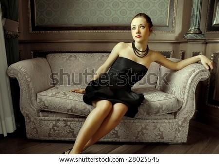 Beautiful woman sitting on a sofa - stock photo
