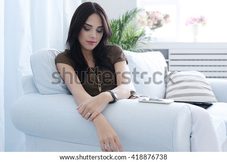 Beautiful woman sitting on a sofa at home