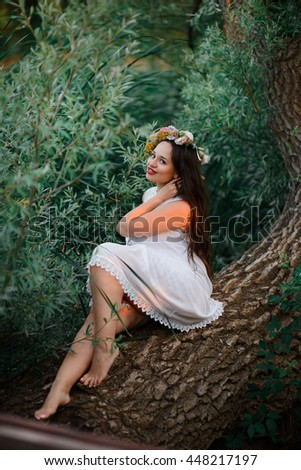 beautiful woman sitting on a tree