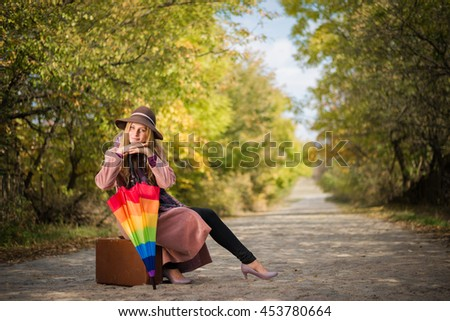 Beautiful woman sitting on a vintage suitcase with umbrella on a desert road - stock photo