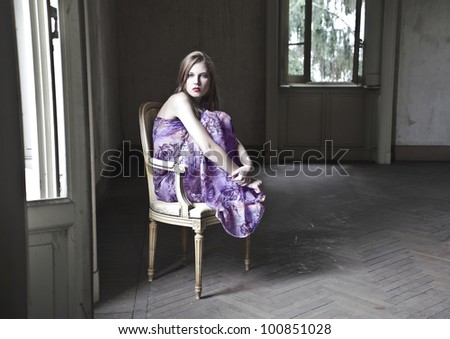 Beautiful woman sitting on an old chair in an empty room - stock photo