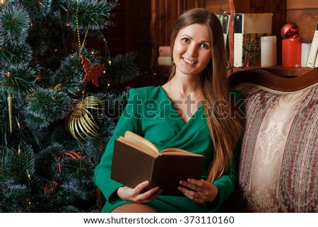 Beautiful woman sitting on armchair and reading book