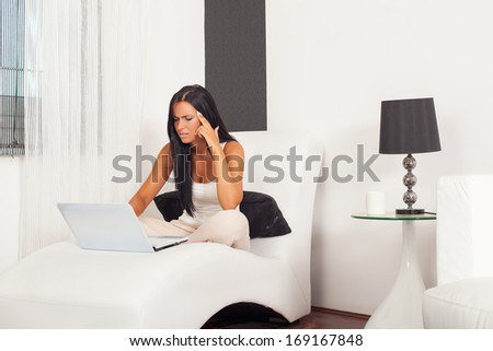 Beautiful woman sitting on armchair with laptop. Selective focus on face.