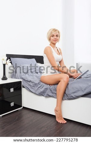 Beautiful Woman sitting on bed using digital tablet, young blond girl in bedroom - stock photo