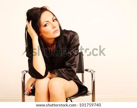 Beautiful woman sitting on chair holding head - stock photo