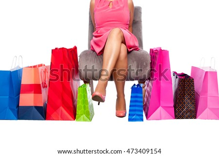 Beautiful woman sitting on chair with colorful shopping bags, commerce lifestyle concept.