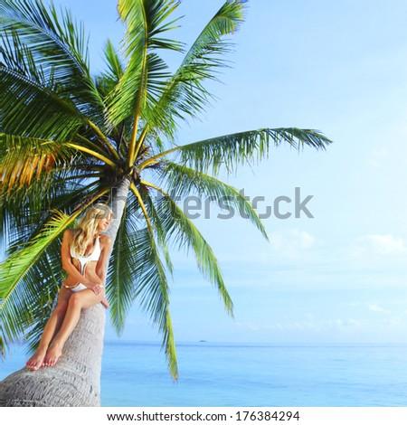 Beautiful woman sitting on palm on sea background - stock photo
