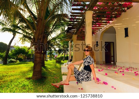 beautiful woman sitting on steps with flower petals around - stock photo