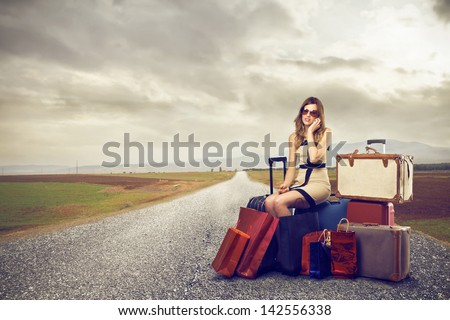 beautiful woman sitting on suitcases in the street talking on the phone