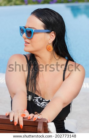 Beautiful woman sitting on sunbed. Woman looking away next to swimming pool  - stock photo