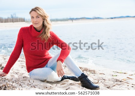 beautiful woman sitting on the beach in winter