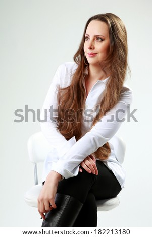 Beautiful woman sitting on the chair and looking away over gray background - stock photo