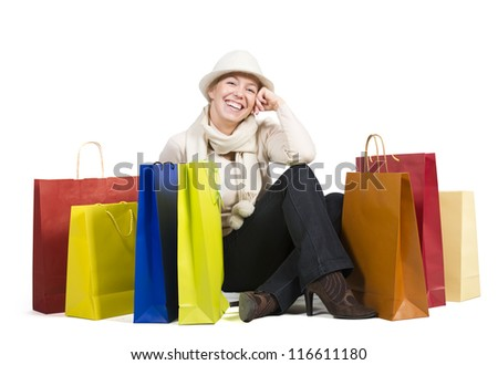 Beautiful woman sitting on the floor surrounded by a lot of colorful shopping bags - stock photo