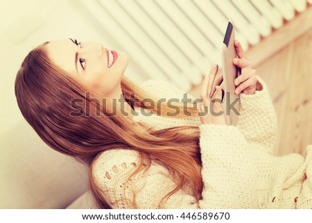 Beautiful woman sitting on the floor with tablet. - stock photo