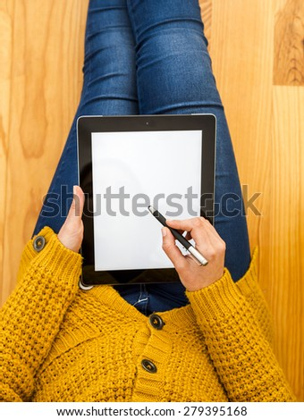 Beautiful woman sitting on the floor working with a tablet  - stock photo