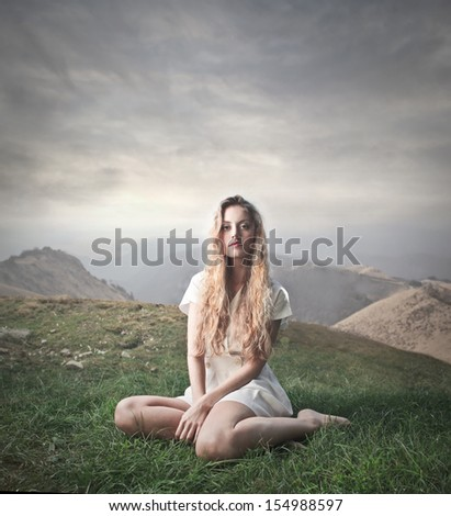beautiful woman sitting on the grass in the mountains