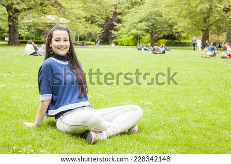 Beautiful woman sitting on the grass looking at camera