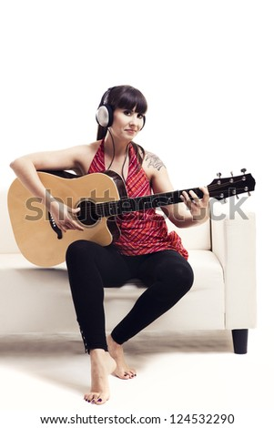 Beautiful woman sitting on the sofa and playing guitar, isolated on white