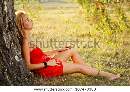 Beautiful woman sitting under tree in park