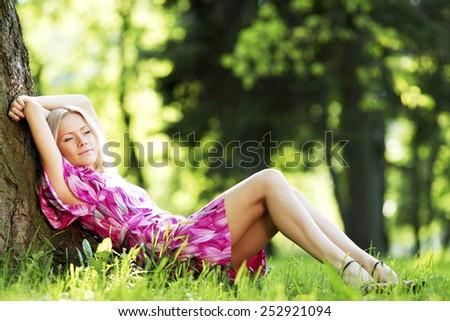 Beautiful Woman sitting under tree in spring park