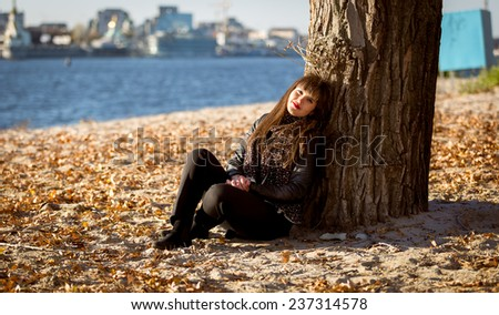 Beautiful woman sitting under tree on beach at sunny day - stock photo