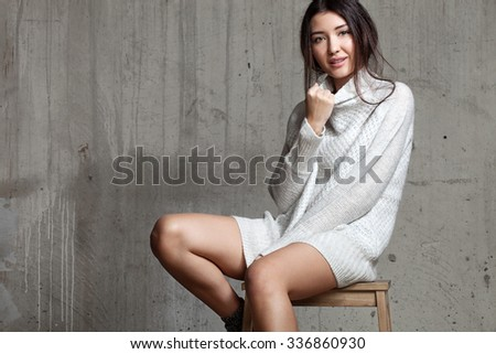 Beautiful woman sitting wearing a cozy winter sweater on the background of a cement wall - stock photo