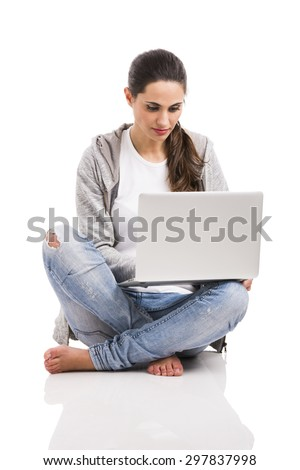 Beautiful woman sitting with crossed legs working with a laptop