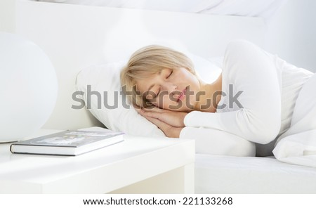 Beautiful woman sleeping in white bed - stock photo
