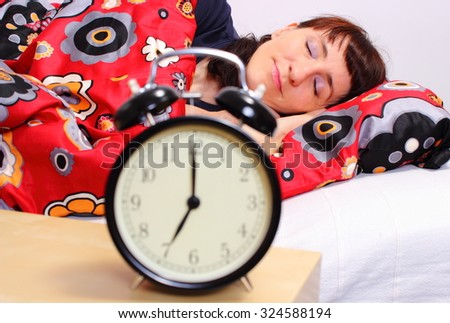 Beautiful woman sleeping on bed in her bedroom and ringing alarm clock - stock photo