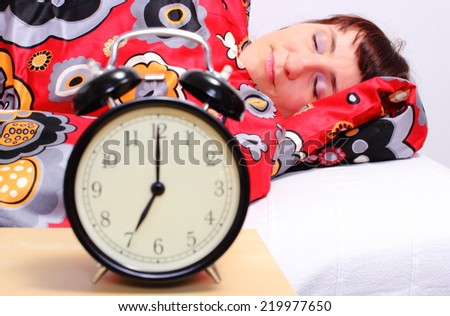 Beautiful woman sleeping on bed in her bedroom with alarm clock - stock photo