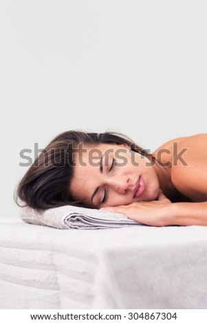 Beautiful woman sleeping on massage lounger in a wellness center isolated on a white background