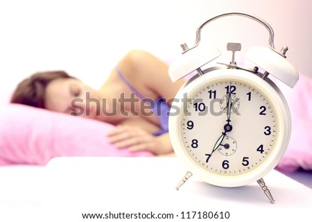 Beautiful woman sleeping soundly and the alarm clock awakens in time,Women and alarm clock,photography