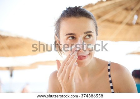 beautiful woman smears face sunscreen at the beach for protection. - stock photo