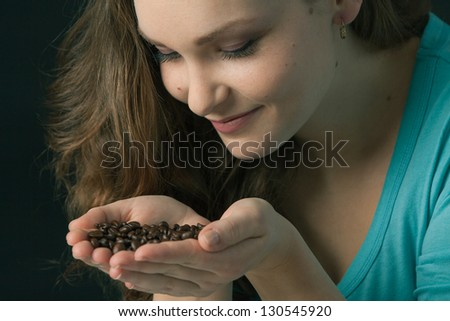Beautiful Woman smelling coffee beans with passion.Young woman holding and smelling coffee beans with an expression of well being. Blue, turquoise shirt.