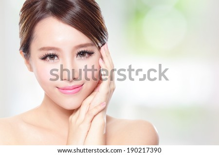 Beautiful woman smile face with clean face skin, concept for skin care, over nature green background, asian