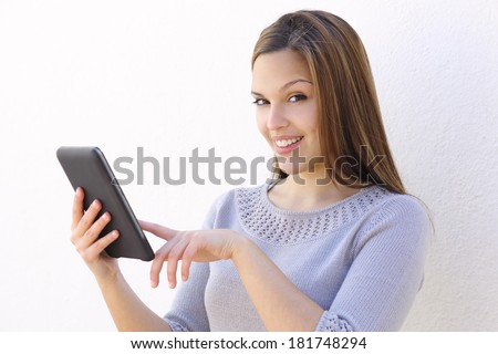 Beautiful woman smiling and holding a tablet reader and looking at camera on a white wall