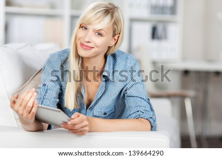 Beautiful woman smiling and holding her tablet over the blurred background