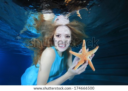 Beautiful woman smiling underwater in the pool with sea star  - stock photo