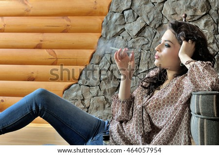 Beautiful woman smokes an electronic cigarette. She sits on the floor next to stone walls and timbered wall indoors
