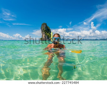Beautiful woman snorkelling in Krabi Thailand taking underwater photographs  - stock photo
