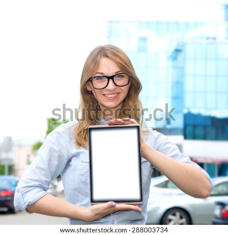 Beautiful woman spectacled holding digital tablet. Female student using touch pad against city background. Freelancer girl working on her digital tablet. Woman browsing with touchscreen device, - stock photo