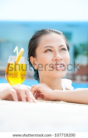 Beautiful woman spending her time in pool with cocktail