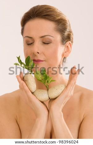 Beautiful woman spoil themselves with the scent of herbs / aromatherapy - stock photo