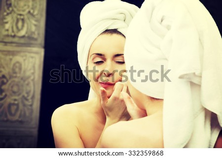 Beautiful woman squeeze her acne in front of the mirror. - stock photo