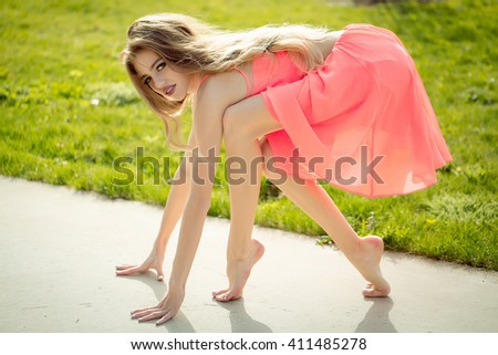 Beautiful woman standing at run start on road in sunny green park in orange dress - stock photo