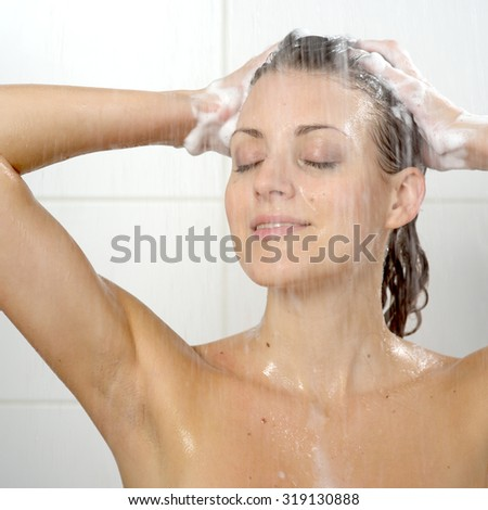 Beautiful woman standing at the shower - stock photo