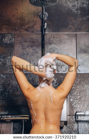 Beautiful woman standing at the shower. is washing her hair. - stock photo
