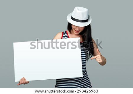 Beautiful woman standing behind, holding white blank advertising board banner in white summer  hat, on gray background - stock photo