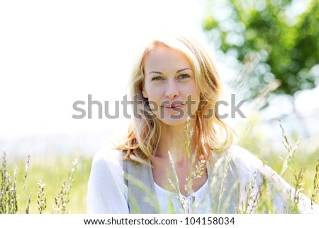 beautiful woman standing in country field in summer time - stock photo